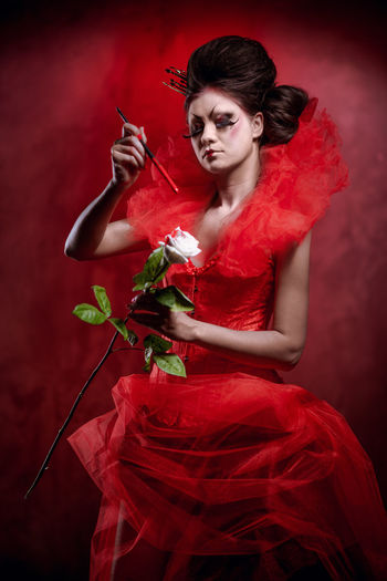 Red Queen. Woman with creative make-up in fluffy red dress with a white rose and paintbrush posing indoors Alice In Wonderland Brunette Brush Character Collar Conceptual Corset Fairy Tale Fictional Character Flower Hairdo Makeup One Person Paint Painting Princrss Queen Of Hearts Red Dress Red Queen Rose - Flower Studio Shot White Background Woman Young Adult Young Women