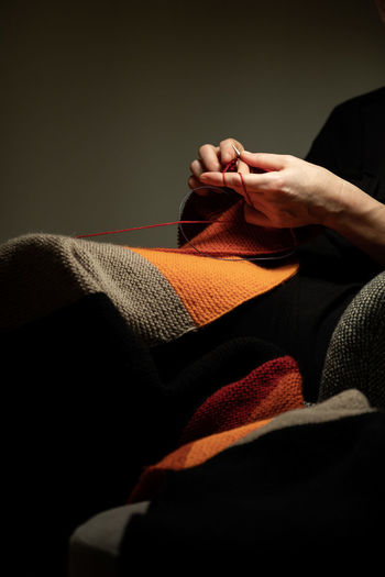 Midsection of woman knitting while sitting against gray background