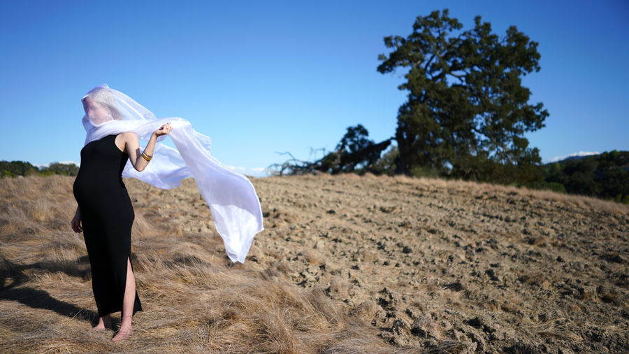 Pregnant woman with scarf covering face standing on land against sky