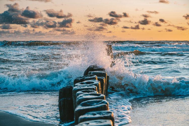 Sea waves splashing on shore during sunset