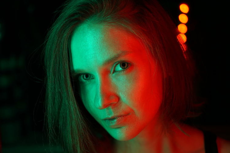 Close-up portrait of beautiful woman with light in nightclub
