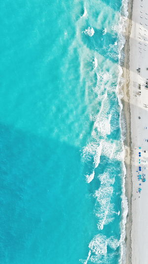 Aerial View Of Sea Waves Rushing Towards Shore