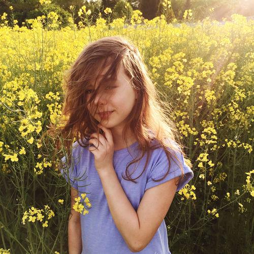Portrait of teenage girl standing at rape farm