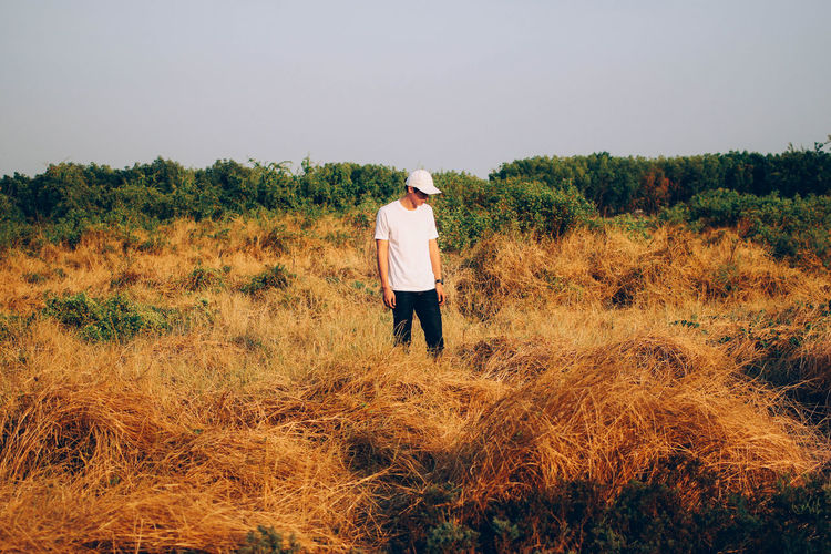 man wearing white t-shirt, cap and jeans standing on the field, copy space EyeEm Best Shots Adult Beauty In Nature Casual Clothing Day Field Full Length Grass Growth Landscape Lifestyles Men Nature One Man Only One Person Outdoors People Plant Real People Rear View Sky Standing Tree