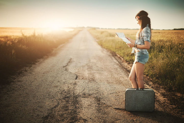 Side view of woman reading map standing by suitcase on road