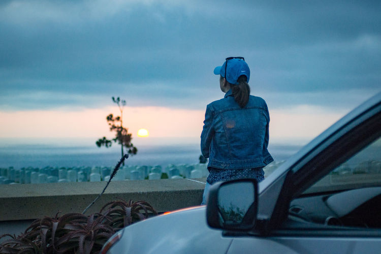 Close-up of man photographing car on sea against sky during sunset