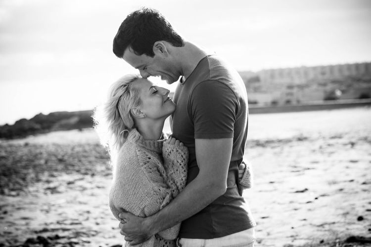 Smiling couple embracing at beach against sky