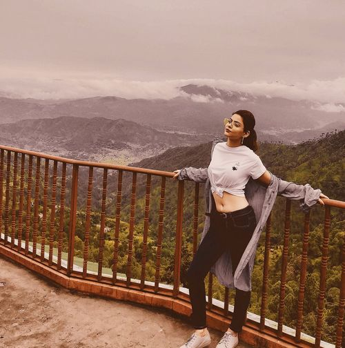 Portrait of young woman standing on railing against mountain