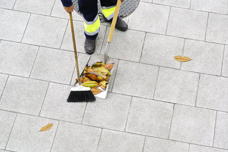 Low section of person cleaning footpath with broom and shovel
