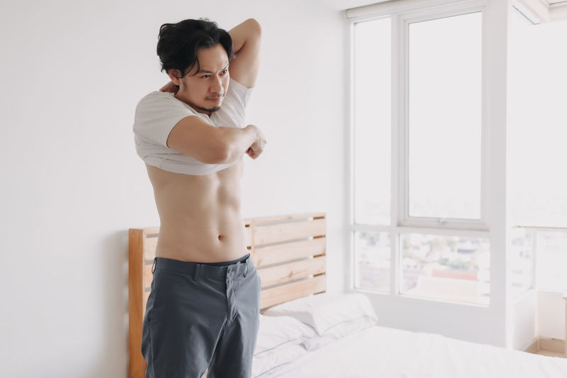Young man looking away while standing on bed at home