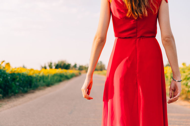 Midsection of woman standing by road against sky
