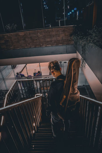High angle view of man carrying guitar on staircase