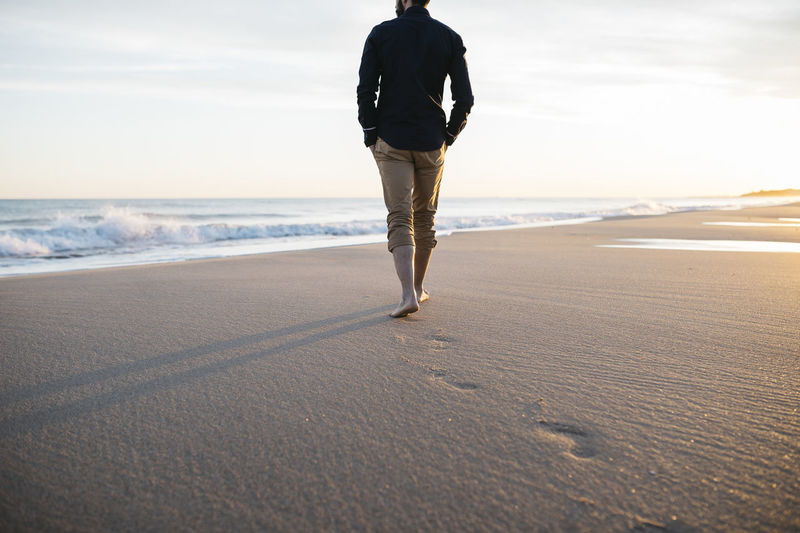 Low Section Of Man Walking At Beach Against Sky