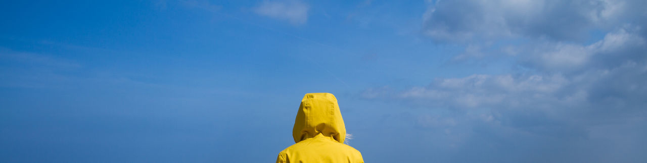 Rear view of woman on a sandy beach wearing a yellow hooded jacket and facing ocean withblue sky.