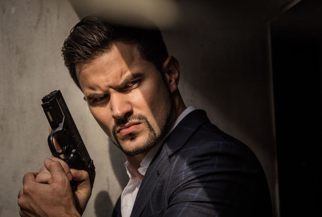 Handsome guy holding a gun Sunlight Adult Businessman Close-up Day Gun Handgun Headshot Holding Indoors  Men One Person People Pistol Real People Serious Suit Suit Man Weapon Weapons Of War Young Adult