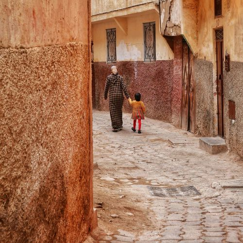 Take my hand, I'll bring you to discover the world. EyeEm Selects Africa Meknès Medina Family Mother Full Length Standing Childhood Architecture Built Structure Building Exterior Children