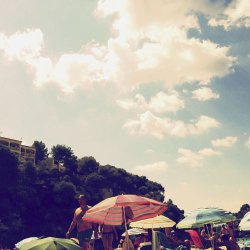 People sunbathing at the beach. Bech Cloud - Sky Crowd Day Leisure Activity Nature Sky Sunbathing Umbrella