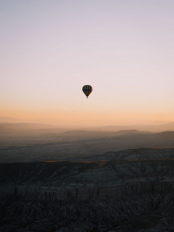 A single balloon rises above the incredible Cappadocia, Turkey Week On Eyeem Balloon Cappadocia Cappadocia/Turkey Turkey Sunrise Hot Air Balloon Landscape Environment Sky Scenics - Nature Sunset Mid-air Orange Color Outdoors Ballooning Festival Flying Tranquil Scene Mode Of Transportation Beauty In Nature Minimalism Aerial View Non-urban Scene Adventure Nature