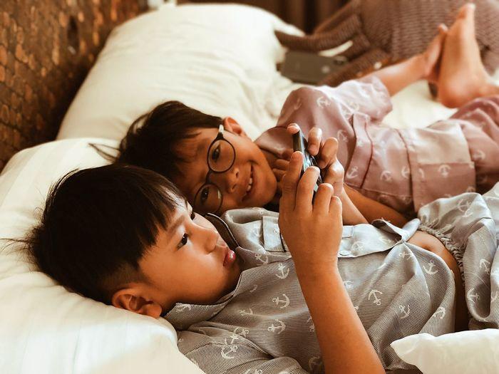 Siblings Looking At Mobile Phone On Bed