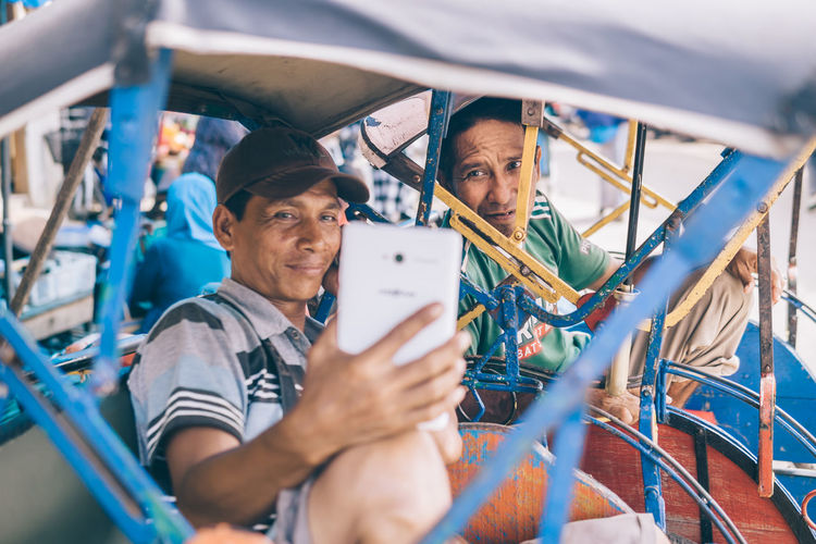 Two Pedicab driver watching movies on the Tablet Adult Adults Only Business Finance And Industry Day Happiness Manual Worker Mature Adult Mature Men Men Only Men Outdoors People Portrait Real People Senior Adult Smiling Street Photography Teamwork Togetherness Two People Young Adult The Photojournalist - 2018 EyeEm Awards The Street Photographer - 2018 EyeEm Awards The Portraitist - 2018 EyeEm Awards A New Beginning A New Perspective On Life