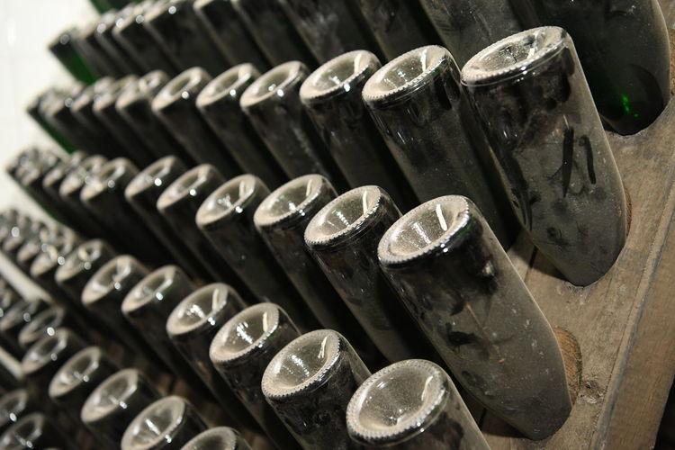 Close-up of old bottles upside down in rack