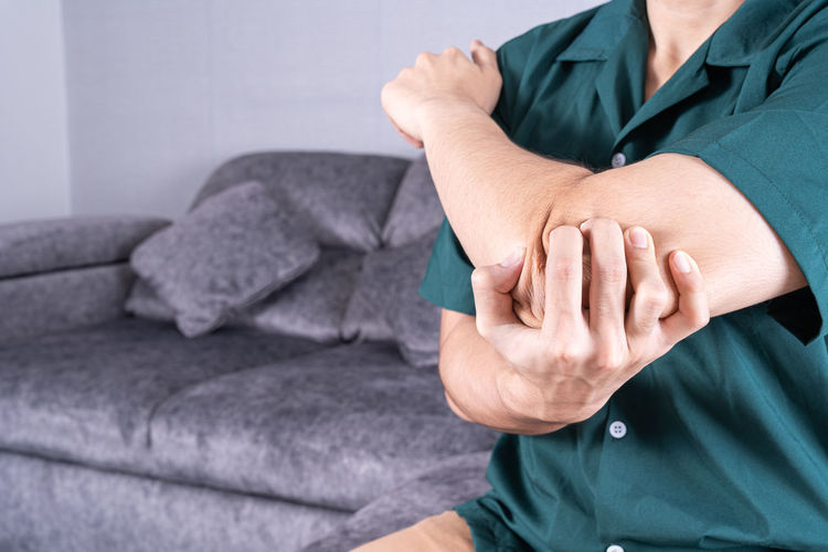 Midsection of man suffering from elbow pain