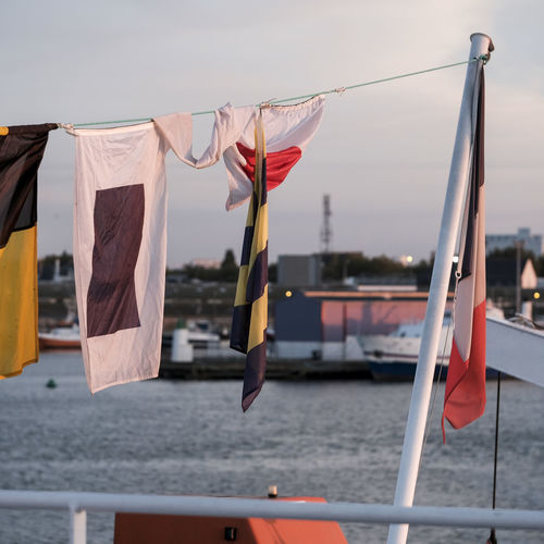 Close-up of flags hanging against boat in sea