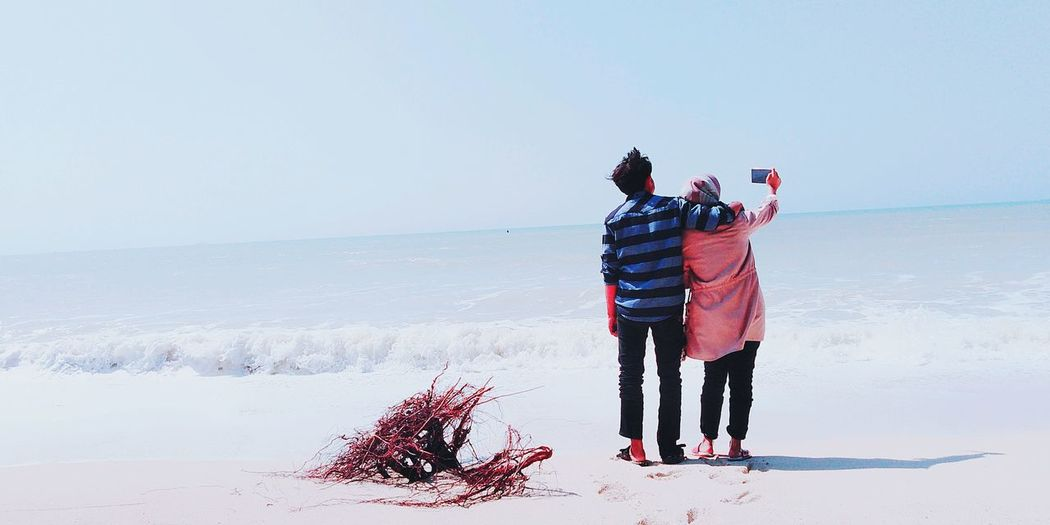 Couple taking selfie at beach against clear sky