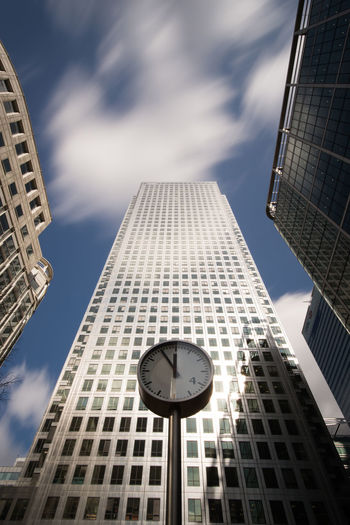 Low angle view of clock against modern buildings in city