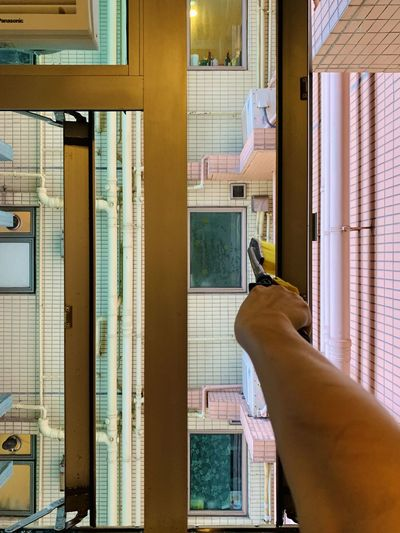 Midsection of woman in glass window at home