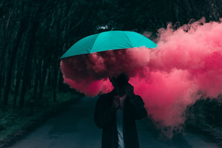 Man holding umbrella while standing with smoke on road in city