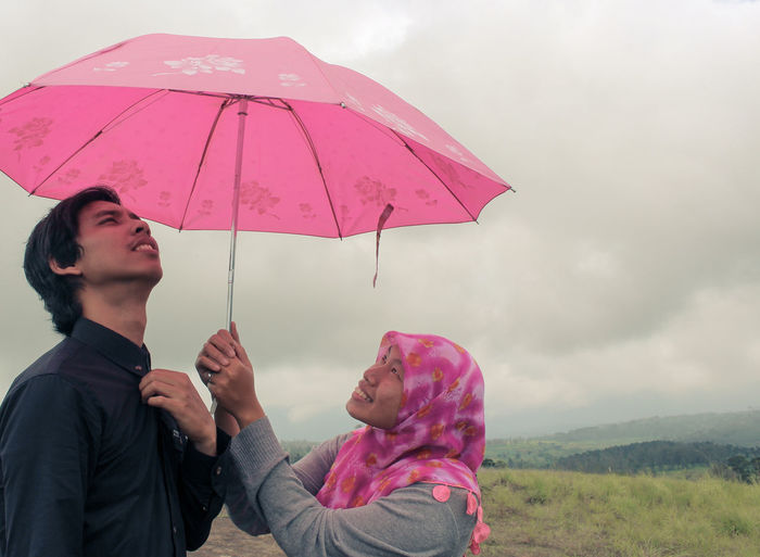 Woman holding umbrella by man against sky during rainy season