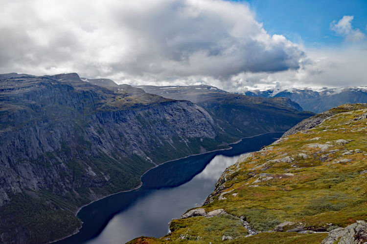 View along Trolltunga hike Norway Beauty In Nature Cloud - Sky Day Environment Idyllic Lake Landscape Mountain Mountain Peak Mountain Range Nature No People Non-urban Scene Outdoors Remote Scenics - Nature Sky Snowcapped Mountain Tranquil Scene Tranquility Trolltunga Norway Hiking Water