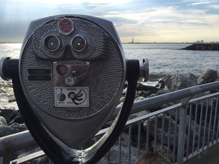 Close-up of coin-operated binoculars by sea against sky