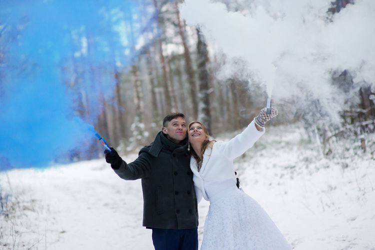 Arms Outstretched Arms Raised Casual Clothing Cold Temperature Day Enjoyment Front View Fun Happiness Human Arm Leisure Activity Lifestyles Love Motion Nature Outdoors Real People Smiling Standing Togetherness Two People Vacations Warm Clothing Winter Women
