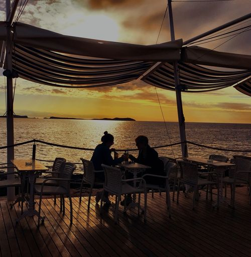 Silhouette couple sitting at restaurant against sea during sunset