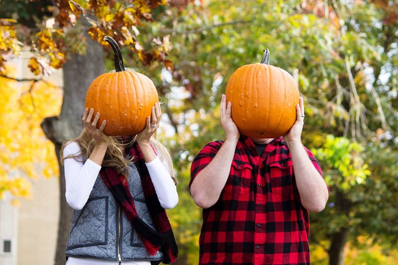 Man and woman hiding face with pumpkins against trees in yard