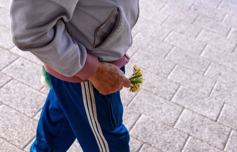 Midsection of man holding flowers while walking on street