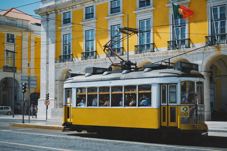 Tram Architecture Building Exterior Built Structure City Day Incidental People Mode Of Transport Outdoors People Real People Sky Street Transportation Yellow Yellow Color