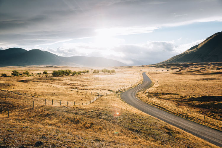 Scenic view of road by mountains against sky