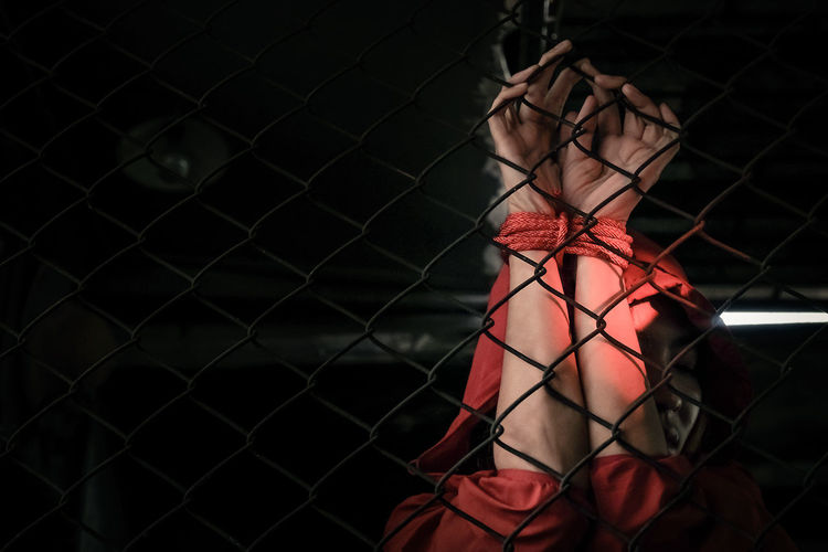 Woman tied with rope behind chainlink fence