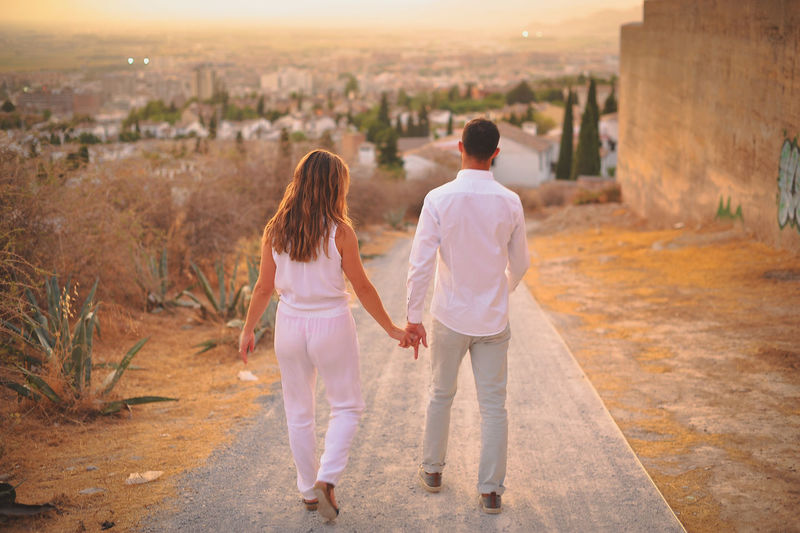 Rear view of young couple walking on road during sunset