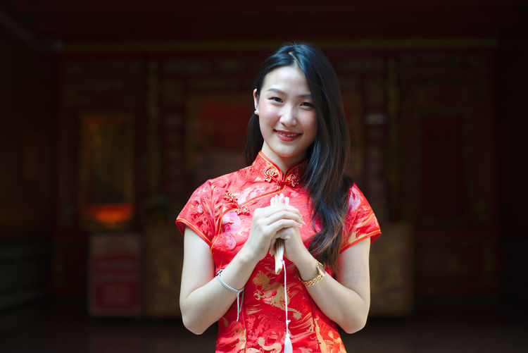Portrait of young woman wearing red traditional clothing while standing outdoors