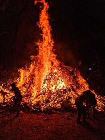 People by bonfire at night