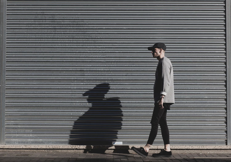 Man standing in front of metal shutter in urban street fashion with shadow. Adult Adults Only Brick Brick Wall City City Life Day Fashion Full Length Hipster Mens Menswear One Person Outdoors People Real People Standing Street Street Fashion Street Photography Urban Urbanphotography Young Adult The Portraitist - 2017 EyeEm Awards