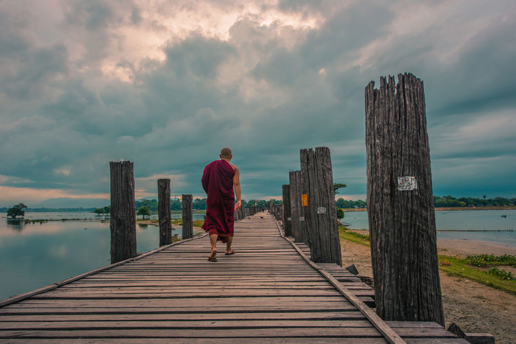 Rear View Of Monk On Pier On Sea Against Sky