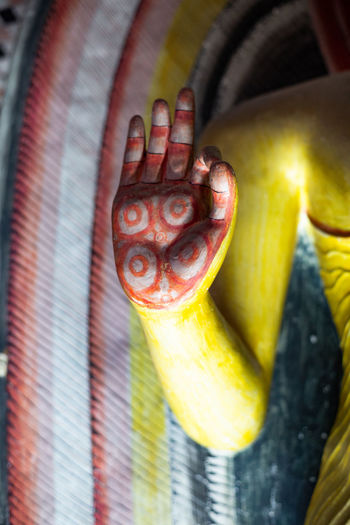A buddhist hand with index finger and thumb clasped together in a cave in Sri Lanka Close-up Real People Hand Human Hand Food Focus On Foreground Yellow Food And Drink Indoors  Day One Person Freshness Human Body Part Vegetable Body Part Nature Buddhism Hand Painted Henna BUDDHISM IS LOVE Buddhist Temple Cave Cave Mural Sri Lanka