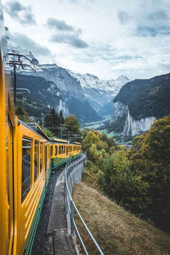Train near mountain range against sky