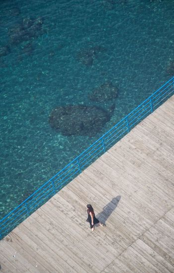 High angle view of woman relaxing on pier