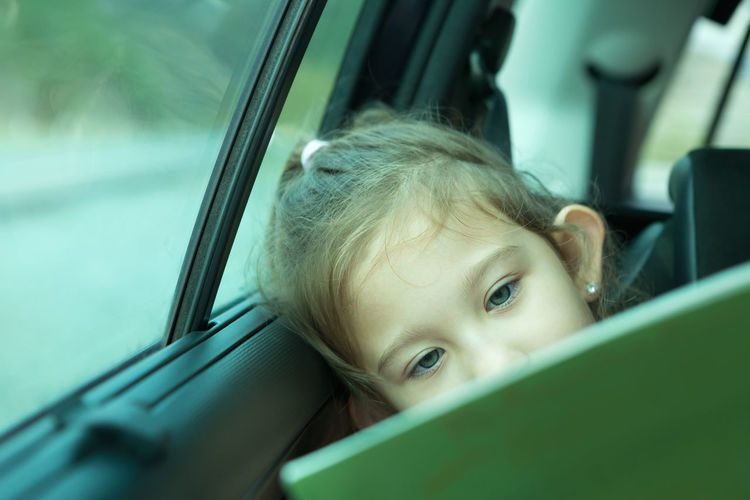 Cute girl reading book in car